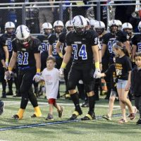 Football team captains hold the hands of children with cancer as they walk out to midfield for the coin toss.