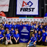 Bensalem High School Robotics Team dressed in royal blue shirts holding a banner naming them Champions