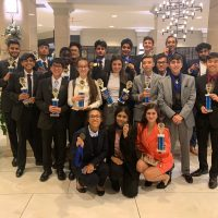 20 Bensalem High School students wearing dresses and suits pose with their trophies
