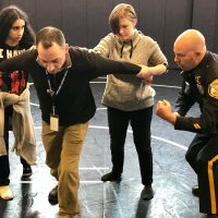Caption: Social Studies teacher Sean Burke is held by two students as School Resource Officer Bob Lee instructs them during volunteer training at Quakertown Community High School.