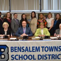 5 men and 9 women, all members of the Bensalem Board of School Directors. 10 are standing behind the 4 sitting at a table with a Bensalem Township School District sign with the district B logo in Blue and Gray