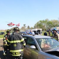 Fire and Emergency Personnel working at a mock car crash scene being staged to show students about impaired driving.