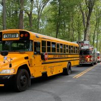 A Levy School Bus leads of caravan of fire trucks as Quakertown Community High School administrators deliver caps and gowns to 2020 grads.