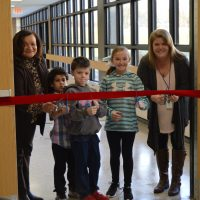 Valley principal with 2 boys, 1 girl, and a female teacher hold scissors on a red ribbon prior to cutting it