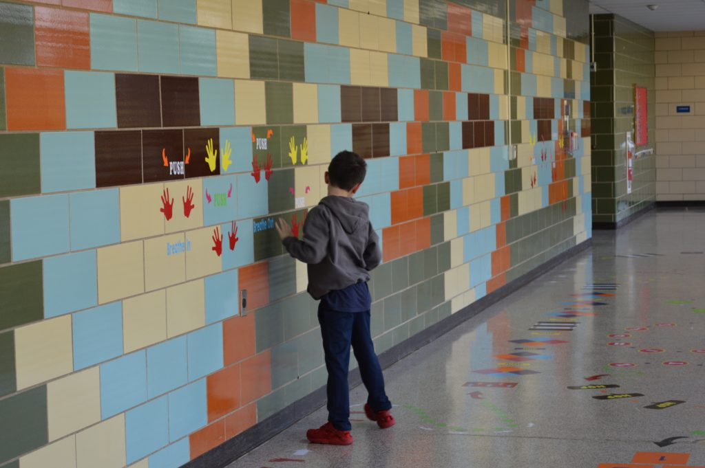 Young boy moving through the sensory paths on the wall. He is placing his hands on the handprints on the wall.