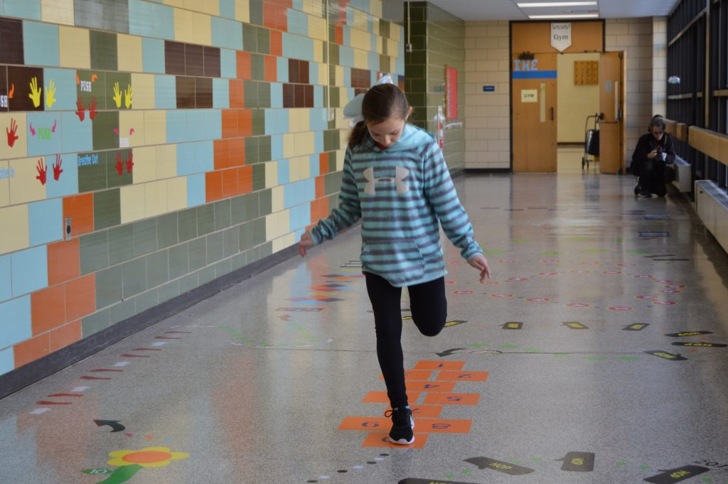 Young girl in a blue and gray shirt and black pants jumps through the sensory path