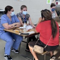 Nurse Melissa Kelly, in blue uniform ar left, and World Language teacher Bethany Fuller, help a parent during QCSD's ELD Resource Night on September 15th.