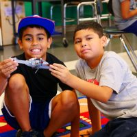 Two ESL male students with a hleicopter they made at Legoland.