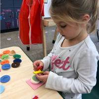 Child uses manipulatives to develop fine motor skills.