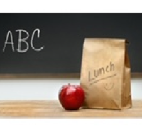 Blackboard with ABC written in capital letters and a brown lunch bag with a red apple sitting next to it