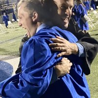 QCHS graduate Mason Smith, left, wearing his blue gown, hugs teacher Nick Hood following the 2021 Commencement Ceremony.