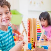 Young child at preschool smiling at the camera while playing