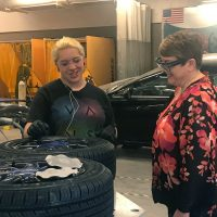 Teenage girl working on a tire in the high school auto shop.