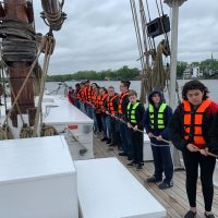 picture of 7th grade students on board the ship holding a rope