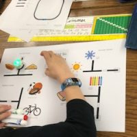 Student shown programming and testing their ozobot robot.