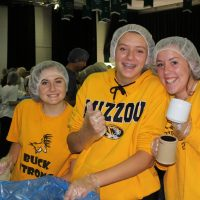 students help fill bags of food for starving children at special event