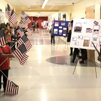 Students wave flags to those entering the building as they pass by posters of photos showing military personnel of the students.