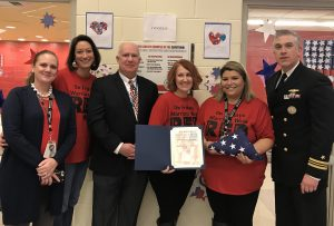Michael Conallen from Rep. Brian Fitzpatrick's office, presents a flag that was flown over the White House to the school staff