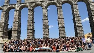 central bucks students stand before an aquaduct in spain