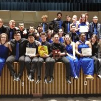 BHS Jazz Ensemble holding their Superior rating plaque. Ladies dressed in royal blue gowns and guys wearing black dress shirts with royal blue ties