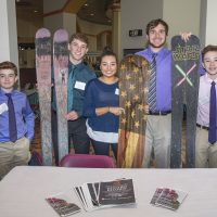 Students proudly holding their snowboards.