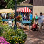 Peddlers Village pathway with flower carts and shoppers strolling