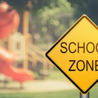 School Zone sign in front of school playground.