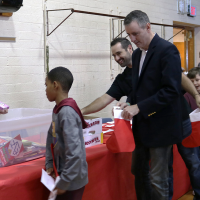 CWO4 (Chief Warrant Officer 4) Kevin Quigley helps a Bucks IU student select items for his stocking as Congressman Brian Fitzpatrick waits his turn.