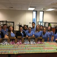 Picture of the Dental stduent with all of the toothbrush item they collected