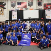 High School Robotics Team, boys and girls, dressed in royal blue shirts holding the blue banner award