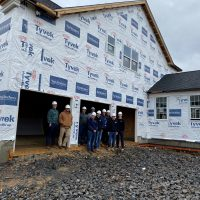 Group of students and their techer in one of the job site with Toll Brothers. They are standing in a framed out house