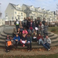 6th grade students sitting on steps with papers in their hands