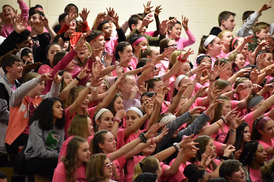 Students in the stands cheering at the Coaches vs. Cancer tournament