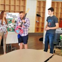 students presenting guitars to local veterans.