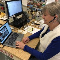 Teacher using a headset for online learning via Zoo