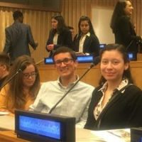 Three students sitting in a lecture hall for a UN Conference