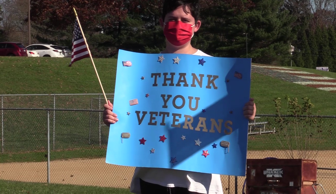 "Student holds a sign that says ""Thank You Veterans"""