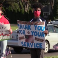 Students hold signs at the Veterans Day Parade at Maple Point MS